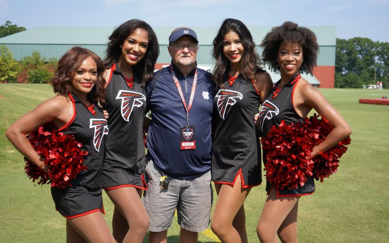 WCHS assistant coach Darrell Dorsey poses for a photo with members of the Atlanta Falcons' dance team during the Falcons' event.