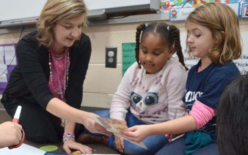 Jack P. Nix Elementary School first-grade teacher Teresa Beckman (from left) speaks with students Brooklyn Moss and Brelyn Austin Dec. 3 during an assignment about needs and wants. (Photo/Stephanie Hill)
