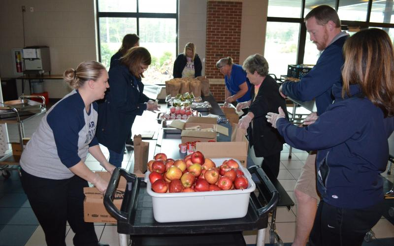 White County School System administrators, White County Middle School administrators and nutrition staff worked hard on Monday, March 16, to pack breakfast and lunches for students. (Photo/Stephanie Hill)