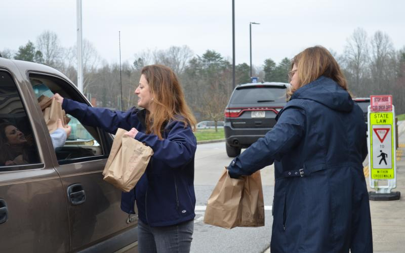White County Schools Director of Student Accountability Jennifer King and Superintendent Dr. Laurie Burkett brought meals to a car in the drive-thru for a student feeding program, which is in place while schools are closed. (Photo/Stephanie Hill)