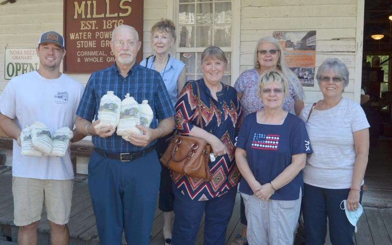 From left, Nora Mill Granary operator Joe Vandegriff presents a donation to Michael Parker, Beth Fine, Ann Helms, Sharon Worrell, Cathy Risener and Wendy Groman. (Photo/Wayne Hardy)