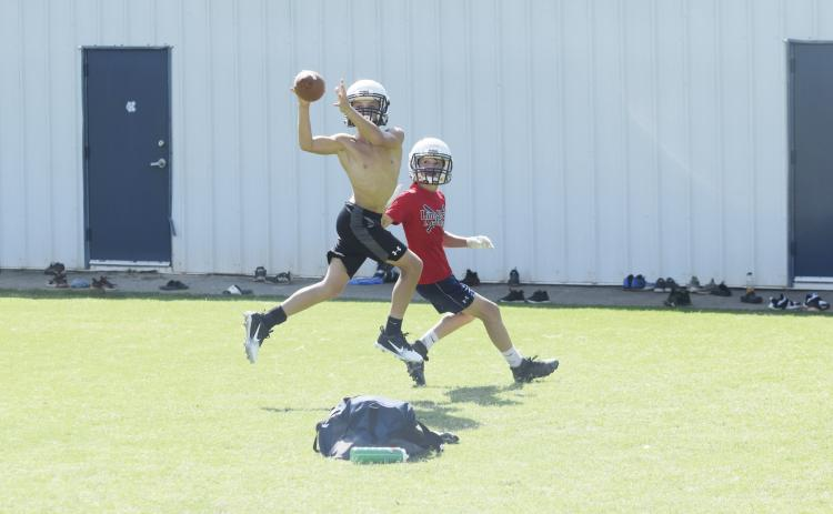 Cam Wilson, left, jumps in front of receiver Trevor Butler to pick off a pass during a one-on-one drill Tuesday morning at the White County Middle School stadium. (Photo/Mark Turner)
