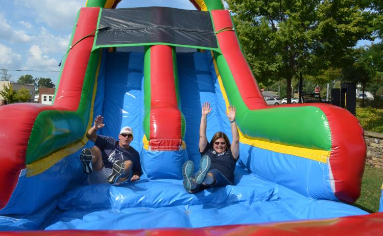 It was a battle of the superintendents as Dr. Laurie Burkett and Scott Justus raced each other down the bouncy slide at the block party held by the White County School System on Sunday, Sept. 15. More photos from the event are in this week's White County News. (Photo/Stephanie Hill)