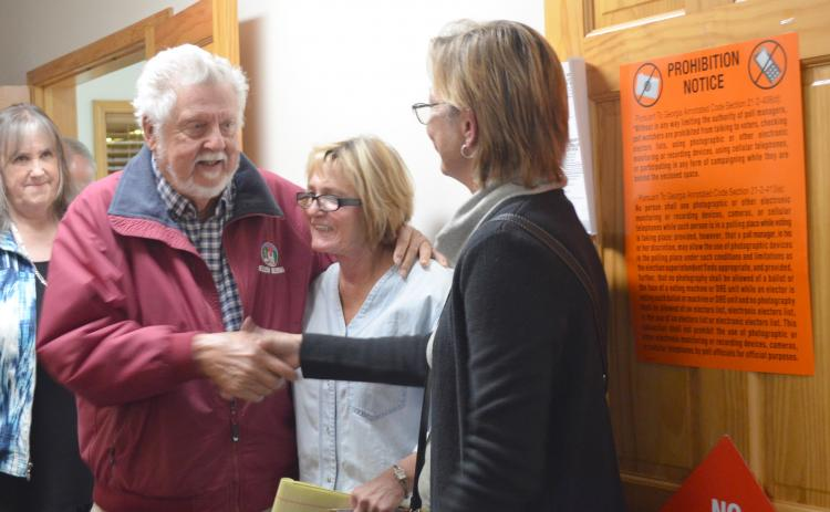 Fred Garmon and Cinnamon Spurlock shake hands after Helen election results are announced. Former city commissioner Dona K. Burke is shown in the middle. (Photo/Stephanie Hill)