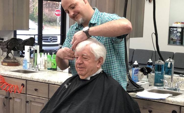 Pharmacist Ray Black sits for the first-ever haircut from Nathan McIntyre at Nate's Barbershop, which opened Monday in Black's new development, Cleveland Drug Plaza on West Kytle Street. Read more about the changes on 7A. (Photo submitted)
