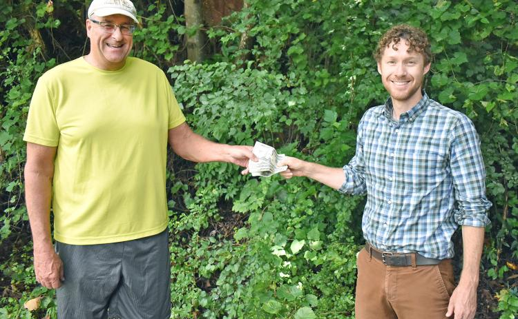 Matt Aiken, The Dahlonega Nugget publisher, hands Patrick Olmsted of Dahlonega, his prize money for winning The Mountain Traveler cover contest. (Submitted photo
