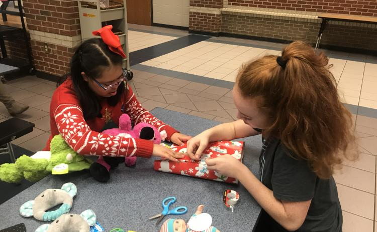 Brooke Puffer and Layla Herbert with Project Unify work together to wrap a present. (Submitted photo)