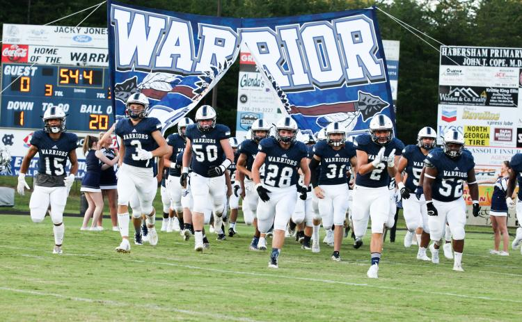 The Warriors, led by, from left, Kane Lowery, Bryson Cronic, Alex Garcia, Seth Stonecypher, Malachi Zellars, Clayton Rogers, and Jaquez Williams charge onto the field for the start of the 2020 season Friday night in Cleveland. (Photo/Staci Sulhoff)