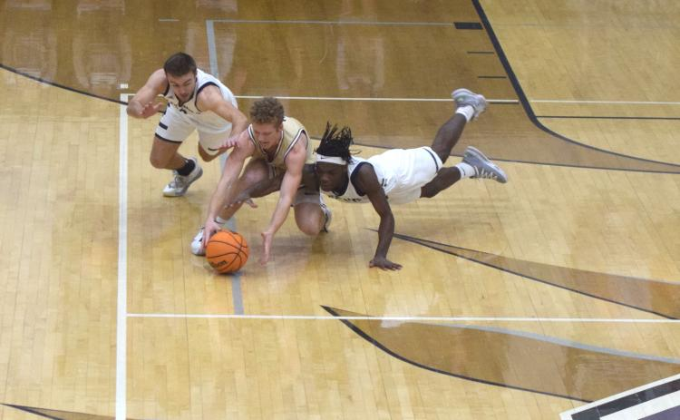 White County's Reece Dockery, left, and Silas Mulligan, and Dawson County's Jadon Gibson dive for a loose ball during the region title game Tuesday in Ellijay. (Photo/Mark Turner)